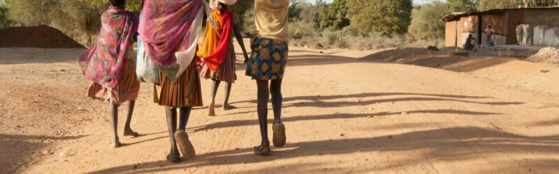 Women walking in village with bags on their heads